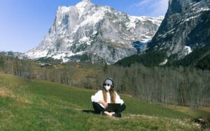 woman wearing a face mask working on her computer in front of a snow-capped mountain